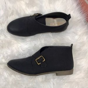 Restricted black buckle flat ankle boots
